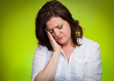 bothered: Depressed, gloomy. Closeup portrait unhappy middle age woman head on hand bothered by mistake situation having bad headache isolated green background. Negative human emotion facial expression feelings
