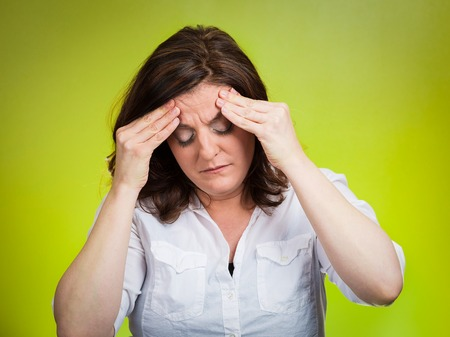 undetermined: Stress headache. Closeup portrait stressed woman having many thoughts, worried about future, thinking isolated green background. Human face expressions, feelings, emotions, life perception, reaction