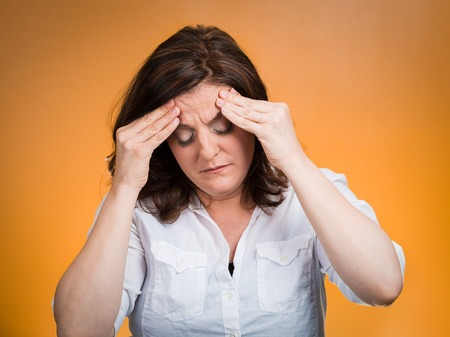 undetermined: Stress headache. Closeup portrait stressed woman having many thoughts, worried about future, thinking isolated orange background. Human face expressions, feelings, emotions, life perception, reaction