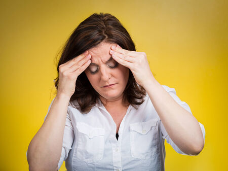 undetermined: Stress headache. Closeup portrait stressed woman having many thoughts, worried about future, thinking isolated yellow background. Human face expressions, feelings, emotions, life perception, reaction Stock Photo