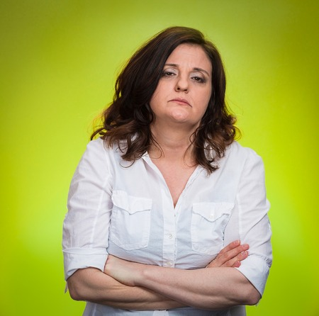 frustrate: Portrait displeased pissed off angry grumpy woman with bad attitude, arms crossed looking at you, isolated green background. Negative human emotion facial expression feeling body language