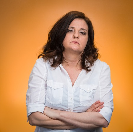 Portrait displeased pissed off angry grumpy woman with bad attitude, arms crossed looking at you, isolated orange background. Negative human emotion facial expression feeling body language