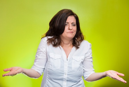 Portrait angry unhappy middle aged woman with arms out asking whats the problem who cares so what I dont know. Isolated green background. Negative human emotions facial expression body language photo