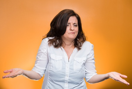 Portrait angry unhappy middle aged woman with arms out asking what's the problem who cares so what I don't know. Isolated orange background. Negative human emotions facial expression body language