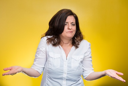 insensitive: Portrait angry unhappy middle aged woman with arms out asking whats the problem who cares so what I dont know. Isolated yellow background. Negative human emotions facial expression body language Stock Photo