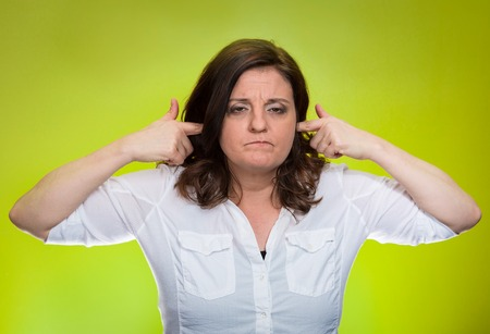 loud noise: Closeup portrait, mature woman covering plugging ears annoyed by loud noise ignoring someone not wanting to hear their your side story isolated green background. Negative human emotion, expression