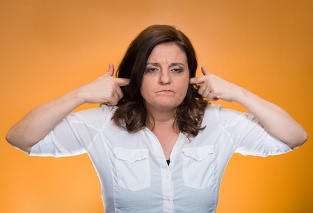 loud noise: Closeup portrait, mature woman covering plugging ears annoyed by loud noise ignoring someone not wanting to hear their your side story isolated orange background. Negative human emotion, expression Stock Photo