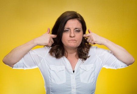 aggressive people: Closeup portrait, mature woman covering plugging ears annoyed by loud noise ignoring someone not wanting to hear their your side story isolated yellow background. Negative human emotion, expression Stock Photo
