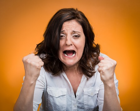 angry women: portrait of young angry woman isolated on orange background  Stock Photo