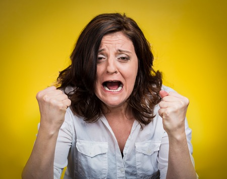 angry teacher: portrait of young angry woman isolated on yellow background
