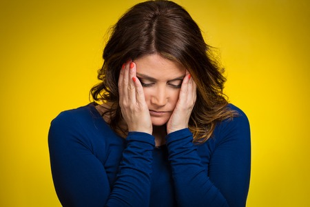 Depressed, gloomy. Closeup portrait unhappy middle age woman head on hand bothered by mistake situation having bad headache isolated green background. Negative human emotion facial expression feelings photo