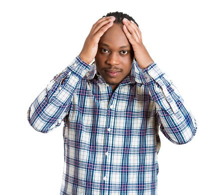 about you: Worried upset stressed. Closeup portrait young serious man thinking about something hands on heard looking at you camera, isolated white background. Negative human emotion facial expression feeling Stock Photo
