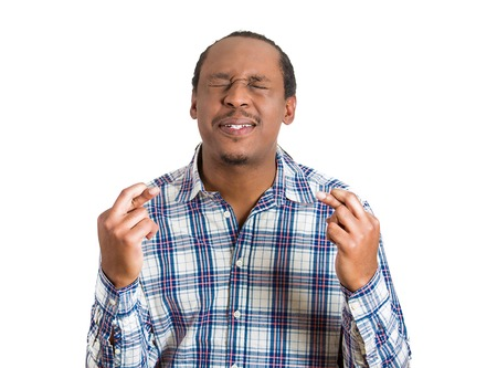 jamaican adult: Portrait young funny guy, business man crossing fingers, wishing, hoping for best, miracle isolated white background. Human emotions, facial expressions, feelings, attitude, body language, gestures