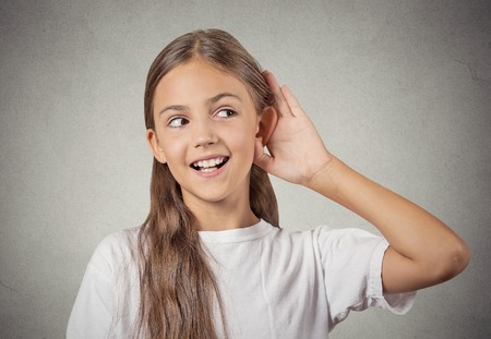 stunned: Curious girl listens. Closeup portrait teenager hearing something, parents talk, hand to ear gesture isolated grey wall background. Human face expression, emotion, body language, life perception