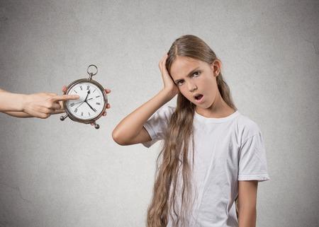 disciplina: Es hora de ir a la cama. Retrato de la madre que muestra el reloj niño que ya es tarde. No le gusta que, aislado fondo de la pared gris. Cara expresiones, emociones. Concepto de crianza Difícil