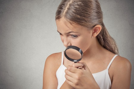 Curious. Child looking through a magnifying glass, isolated on grey wall background. Human face expressions photo
