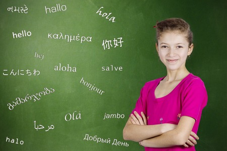 spanish language: Learning foreign languages. Portrait confident teenager girl student standing by chalkboard with word hello written in different foreign languages. Education concept, international communication