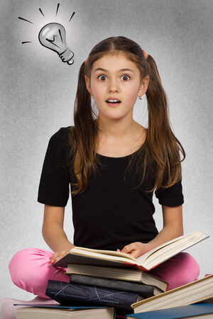 aha: Kids learn. Portrait intelligent surprised girl came up with idea reading book aha, isolated  background with lighting bulb. Positive human emotions, facial expressions, perception. Education concept