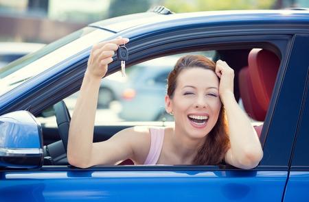Close-up portret gelukkig, glimlachen, jonge aantrekkelijke vrouw, koper zitten in haar nieuwe blauwe auto met sleutels geïsoleerd buiten dealer, dealer veel, kantoor. Persoonlijk vervoer, auto aankoop begrip Stockfoto - 31846689