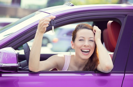 purple car: Closeup portrait happy, smiling, young attractive woman, buyer sitting in her new purple car showing keys isolated outside dealer, dealership lot office. Personal transportation, auto purchase concept