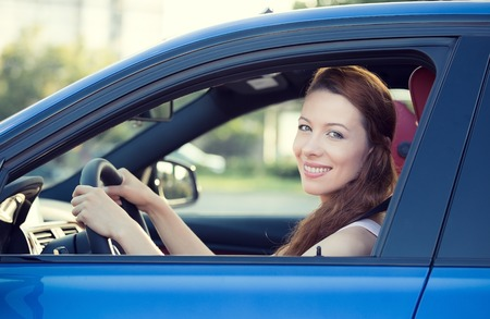 safe driving: Portrait smiling, attractive happy woman, buckled up, driving, testing her new blue car, automobile, purchased at dealership, isolated street, city traffic background. Safe driving habits concept Stock Photo