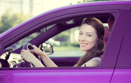 Portrait smiling, attractive happy woman, buckled up, driving, testing her new violet car, automobile, purchased at dealership, isolated street, city traffic background. Safe driving habits concept photo