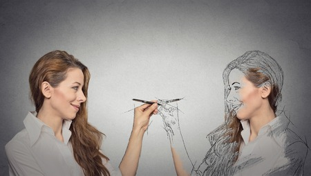 personalities: Create yourself, your future destiny, image, career concept. Attractive young woman drawing a picture, sketch of herself on grey wall background. Human face expressions, determination, creativity