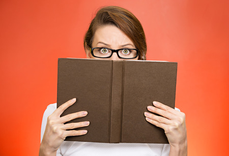 secret information: Shy, secret. Closeup portrait woman with glasses hiding face behind book looking at camera suspicious isolated red background. Education concept. Face expression, life perception. Girl holding book