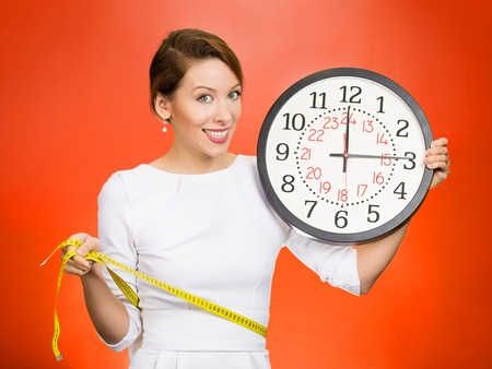 self conscious: On time great fitness result. Portrait young attractive happy fit woman holding clock, measuring her waist with tape isolated on red background. Weight loss fitness program. Positive face expression Stock Photo