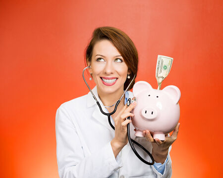 time deficit: Portrait happy health care professional, doctor, nurse listening with stethoscope to piggy bank, dollar bill, isolated on red background. Medical insurance, medicare reimbursement, reform concept Stock Photo