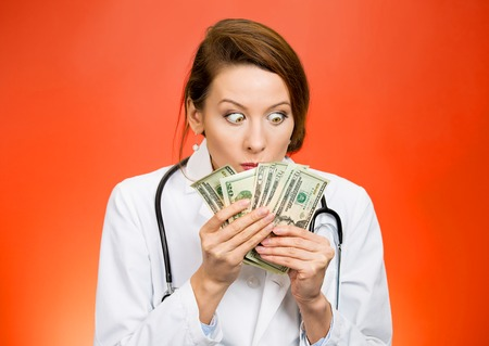 reimbursement: Greed. Portrait miserly health care professional female doctor holding looking at her money dollars in hand fascinated isolated red background. Negative human emotion facial expression life perception Stock Photo