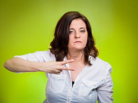 cut off head: Cut it out all nonsense. Portrait angry woman gesturing to stop talking or she will take your head off isolated green background. Negative emotion face expression feeling non verbal communication Stock Photo