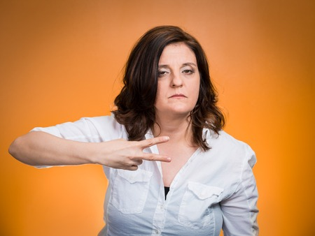 cut off head: Cut it out all nonsense. Portrait angry woman gesturing to stop talking or she will take your head off isolated orange background. Negative emotion face expression feeling non verbal communication