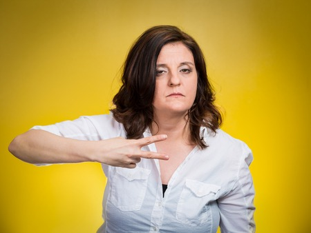 cut off head: Cut it out all nonsense. Portrait angry woman gesturing to stop talking or she will take your head off isolated yellow background. Negative emotion face expression feeling non verbal communication Stock Photo