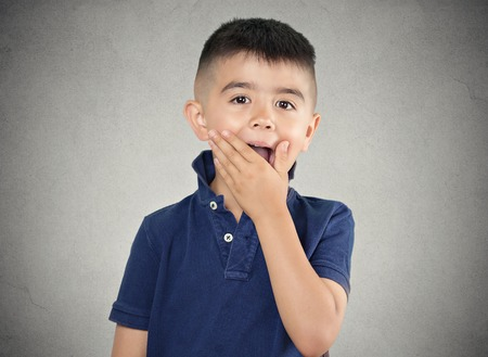 Child surprised. Closeup portrait headshot boy with astonished face expression, opened mouth, isolated grey wall background. Human emotions, body language, perception. Unexpected discovery, reaction photo