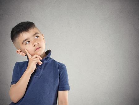 Aspiraties. Close-up portret, headshot denken, dagdromen kind jongen vinger op het gezicht, opzoeken, geïsoleerd grijze muur achtergrond. Positieve menselijke gezichtsuitdrukking, emoties, gevoel leven perceptie