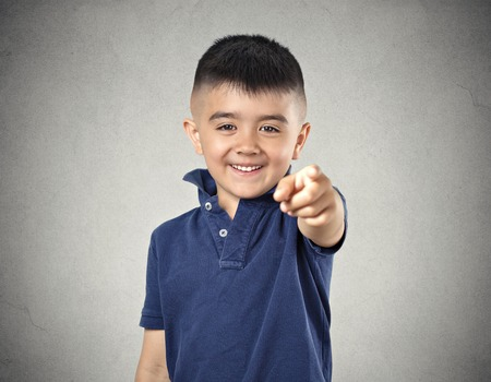 fullness: Laughter. Portrait boy laughing pointing finger at someone something, at camera gesture isolated grey wall background. Positive human face expression emotion feeling attitude life situation perception