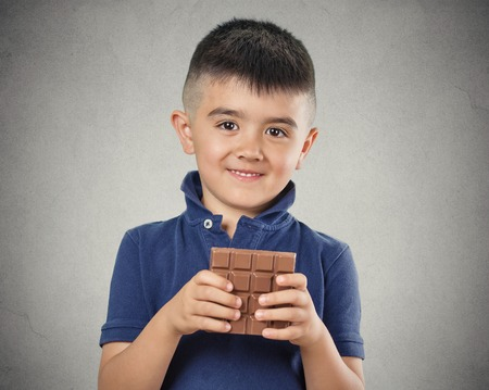 rewards: Kids love sweets. Portrait happy little boy eating whole bar of chocolate, isolated on grey wall background. Positive human emotions, face expressions. Food cravings
