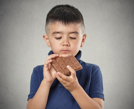 chocolaty: Kids love sweets. Portrait happy little boy eating whole bar of chocolate, isolated on grey wall background. Positive human emotions, face expressions. Food cravings