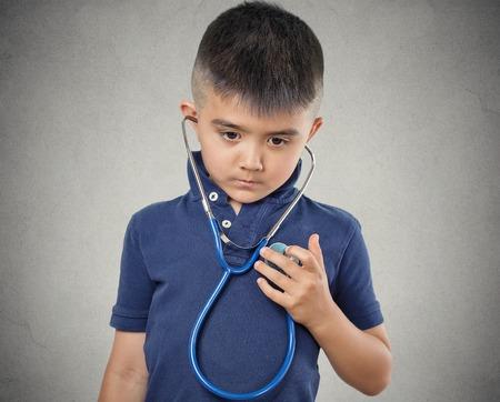 heart disease: Retrato del primer niño niño pequeño escuchando a su corazón con el estetoscopio aislado fondo de la pared gris. Los niños de la salud la atención médica, la medicina preventiva, el concepto de auto-evaluación. Expresión de la cara