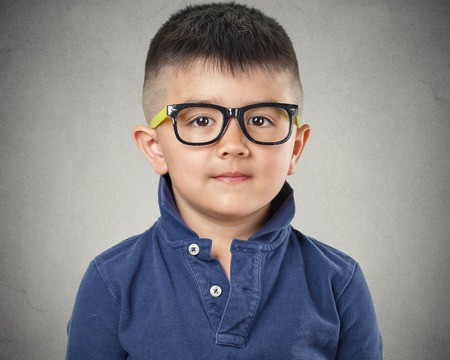 Portrait happy child with glasses on grey wall background. Face expressions Stock Photo