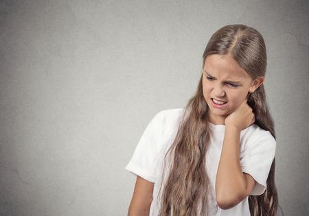목 통증. 세로 스트레스 불행 어린 십 대 소녀 여자 허리 통증, 격리 된 회색 벽 배경을 공부하는 긴 학교 시간 후. 부정적인 인간의 감정 표정의 감정 스톡 콘텐츠