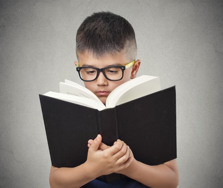 asian medical: closeup portrait child boy with glasses reading holding book too close having difficulty to see text, isolated grey wall background. Face expressions. Education concept. Vision problems in children Stock Photo