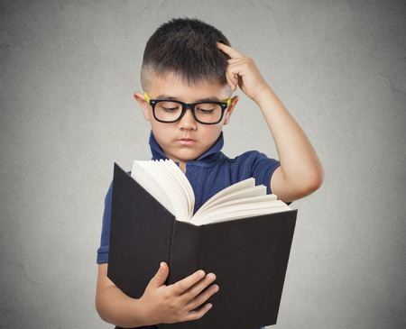 closeup portrait child with glasses reading book, isolated grey wall background. Face expressions. Education concept photo