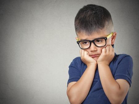 ansiedad: Triste, el pensamiento. Headshot Retrato del primer deprimido, solo, niño cansado que se reclina la cabeza en el puño aislado fondo de la pared gris. Vida sintiéndose negativo expresión cara emoción humana lenguaje corporal percepción