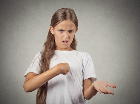 lack of confidence: Closeup portrait surprised teenager girl getting unexpected attention from people asking you talking to, mean me? pointing finger at herself isolated grey background. Facial expression body language Stock Photo