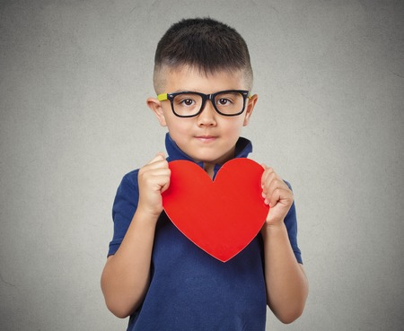 Child holds red heart, isolated grey wall background. Positive human emotions, feelings, attitude, life perception, face expressions. Compassion concept photo