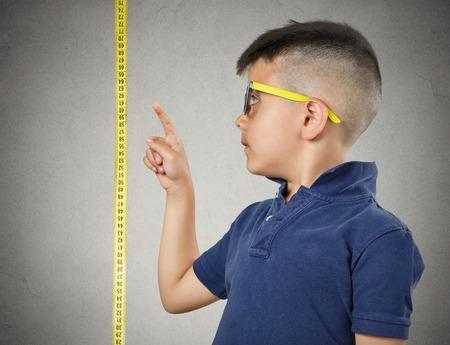 Я рос. Ребенок с очки, указывая на его высоту на рулетка рядом с ним, серый фон стены. Дети концепция развития. Выражение лица
