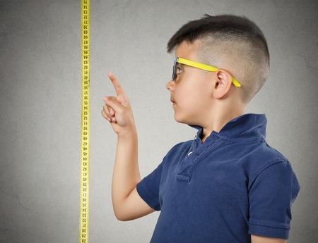 measure height: Im growing up. Child with glasses pointing at his height on measuring tape beside him, grey wall background. Children development concept. Face expression