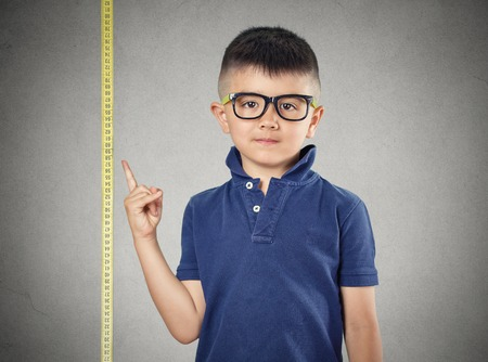 I'm growing up. Child with glasses pointing at his height on measuring tape beside him, grey wall background. Children development concept. Face expression